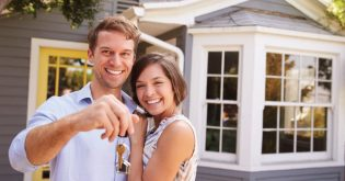 A young couple hold up the keys to their new house after buying their first home