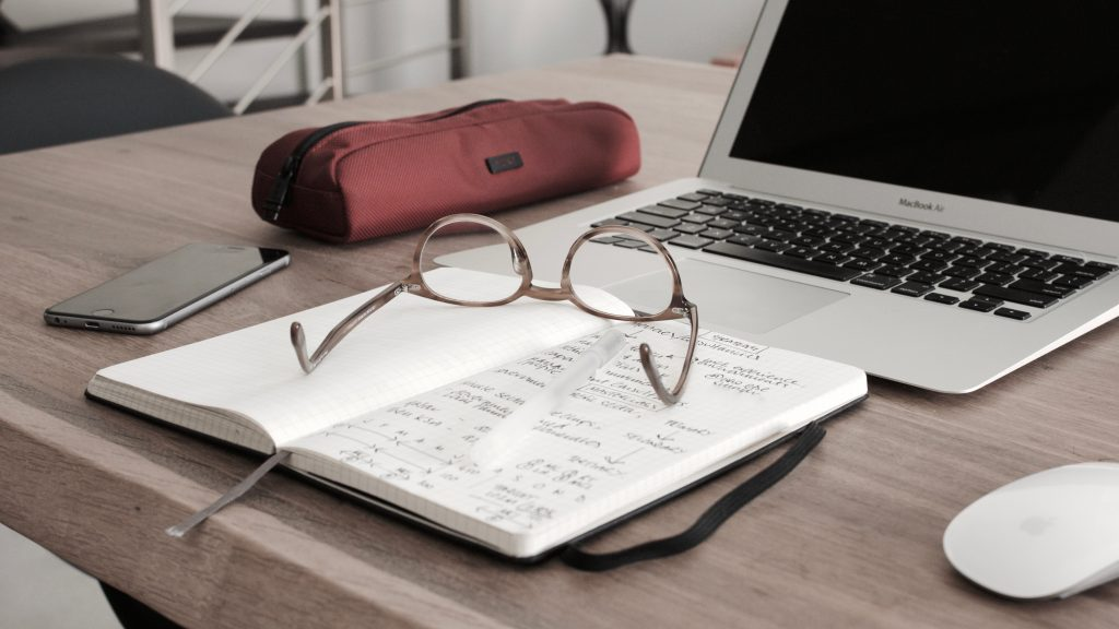 Student workbook, glasses and laptop