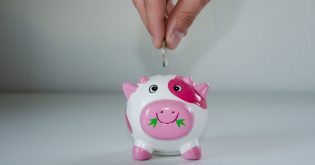 A hand placing a coin in a piggy bank