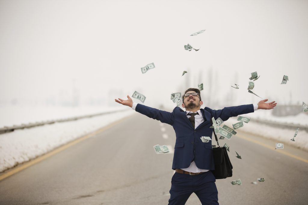 Man with money flying around him on the street