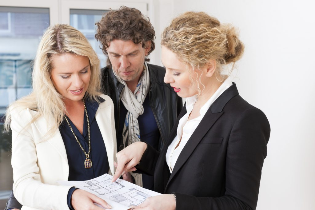 Young realtor explain lease agreement or purchase contract with floor layout to couple in an apartment, close-up