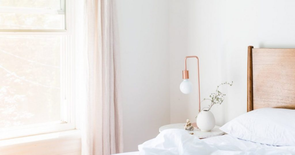 A white bed and a copper bed lamp in a bedroom with white walls.