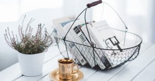 A basket with books and a coffee cup for staging a home when selling a house