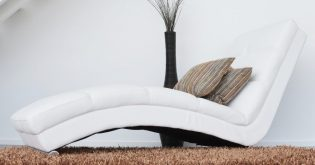 A white couch with brown cushions