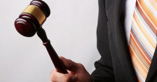 A real estate agent practices common auction strategies with a gavel in hand