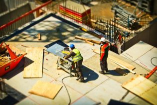 Two construction workers work on a property development project