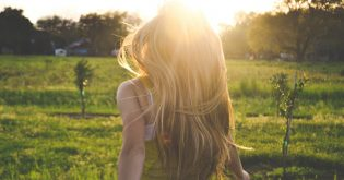 A girl walks in a green field with the sunset glowing in her hair as she walks to her green home