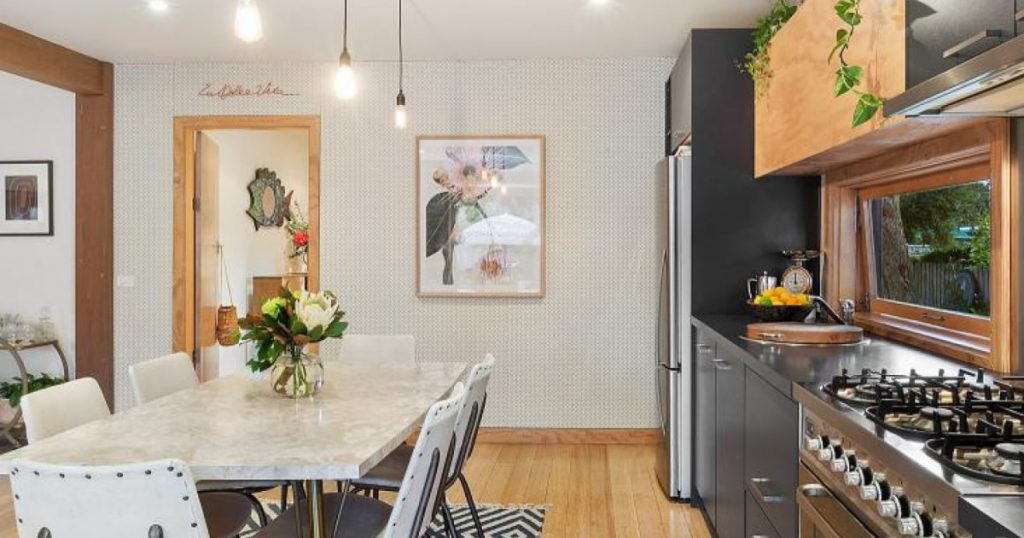 A Home Staged Kitchen With A Marble Table, Wooden Floors And Charcoal  Cupboards