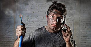 A man holds a wire that has just blown up as he is on the phone to an electrician