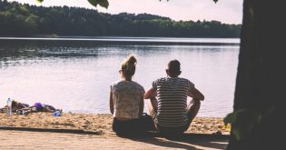 A young de facto couple sitting by a lake possibly contemplating the real estate market