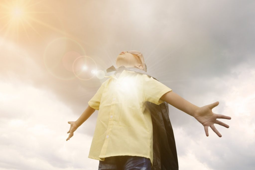 A boy in a cape peers up at the sky with his arms outstretched