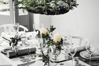 A table decorated for Christmas lunch with white candles and green flowers.