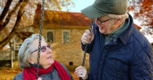 Older couple on a swing and looking at one another