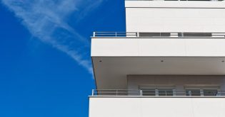 An white concrete investment property set in front of a blue sky