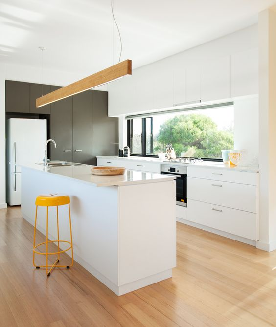 A bright, white kitchen with a central kitchen island and a timber hanging light.