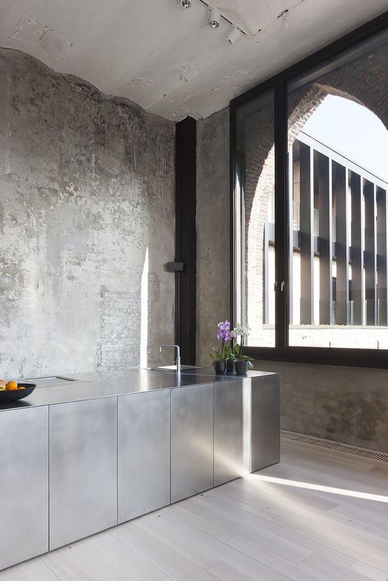 A concrete, bare and minimalist modern kitchen design.