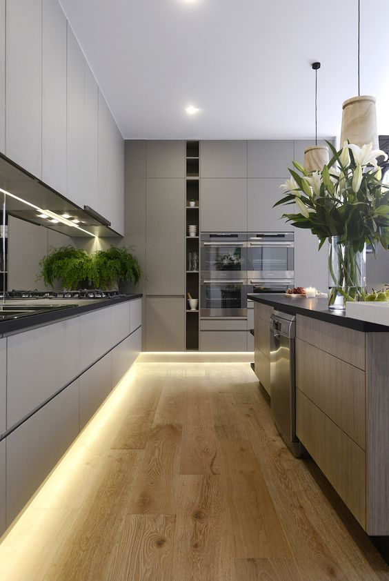A light charcoal kitchen with lilies on the kitchen island bench top.