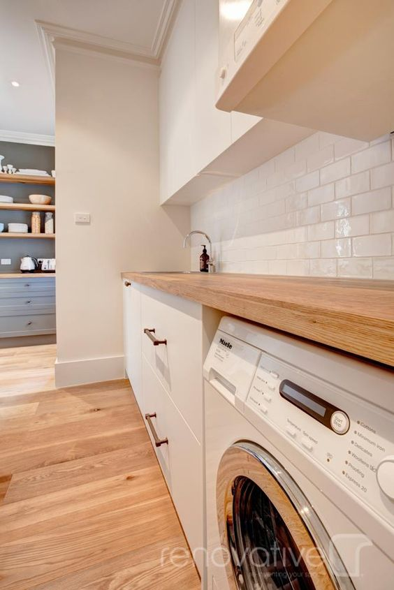 A laundry with a timber bench top and a sink in the background.