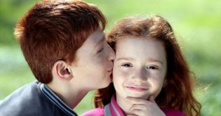 A boy kisses his sisters cheek