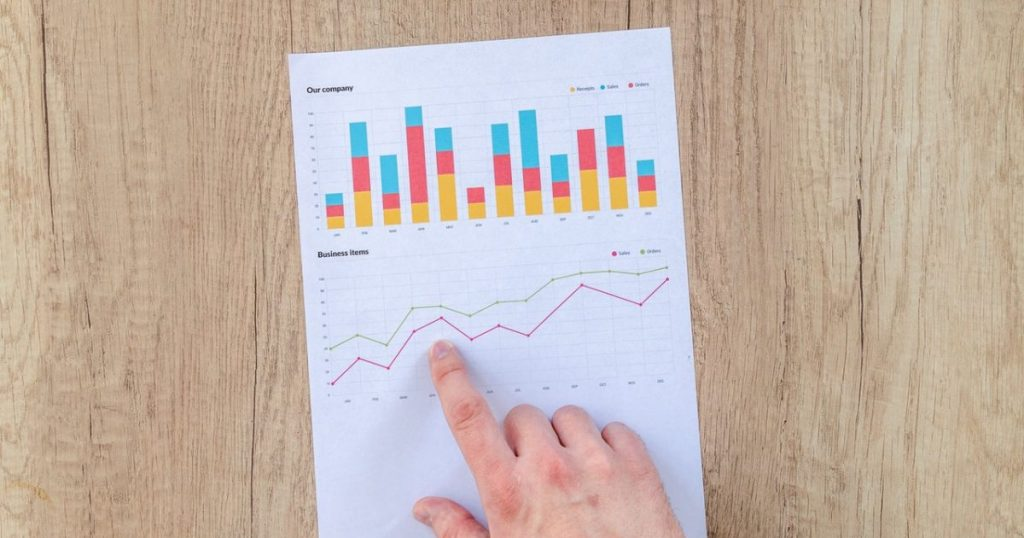 Finger points to a graph on a wooden table and evaluates a rental yield.