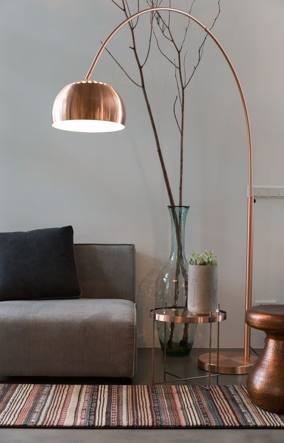 A copper floor stand light overlooking a grey low-seated couch.