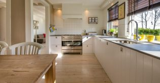 A bright, modern L-shaped kitchen design with timber flooring.