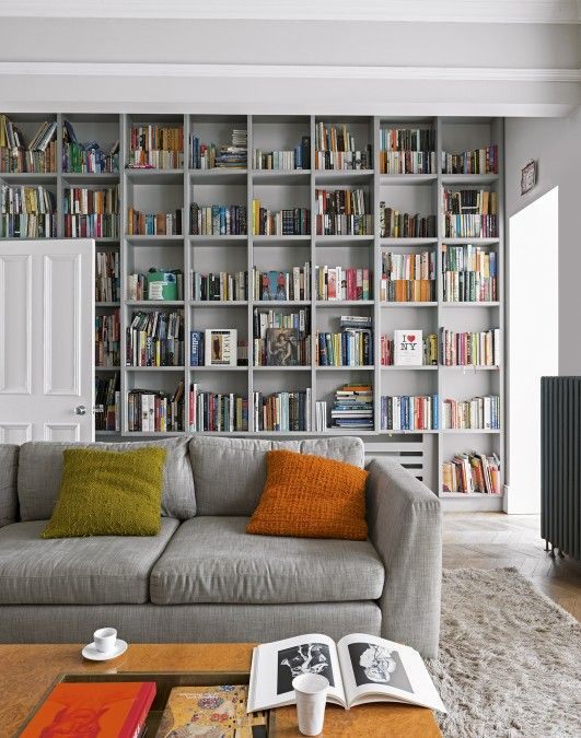 A grey couch with two cushions sits in the foreground, while a wall long bookshelf sits in the background filled with books.