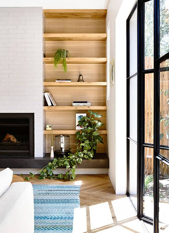 A wooden inset bookshelf sits between a large window and a fireplace framed in white brick.