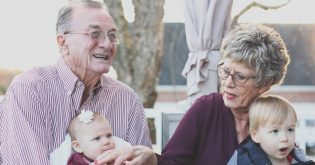 An older couple hold their grandchildren for an article on reverse mortgages.