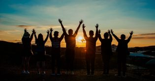 People waving their arms in front of a sunset for an article about sunset clauses
