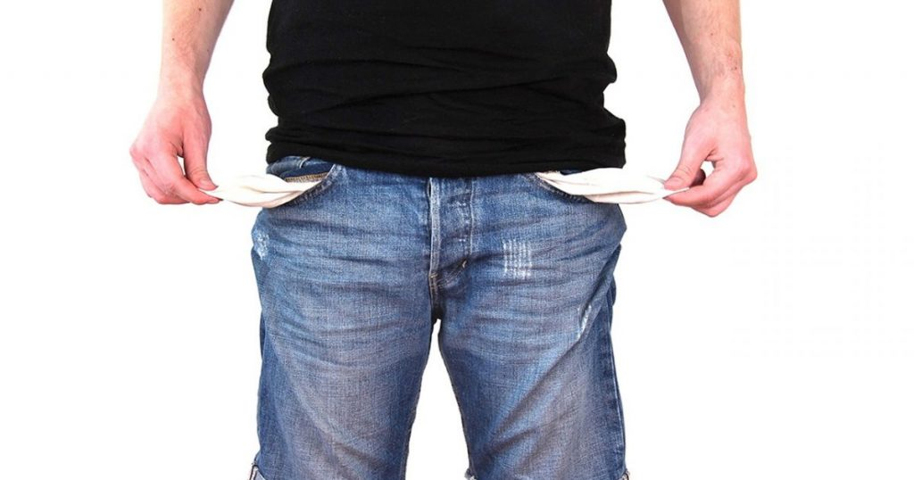 A man holds his empty pockets out