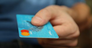 An independent mortgage broker holds out a blue credit card