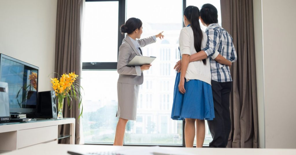 Estate agent showing married couple the view from the apartment window