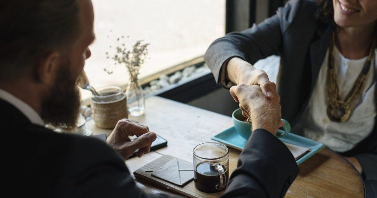 Two people shake hands and agree on a real estate agent fees