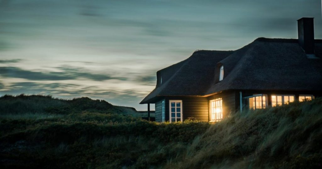 A home at dusk with a light on in the window