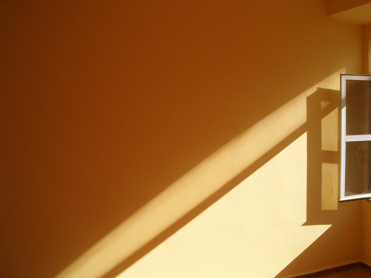 Light filters through a window onto a yellow wall