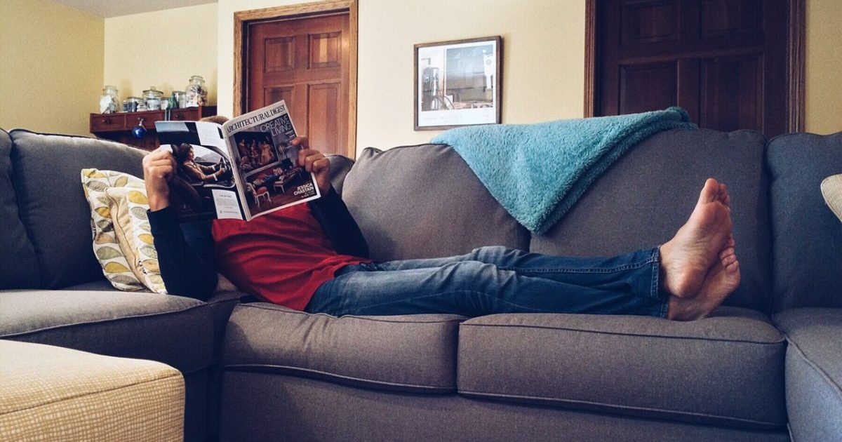 A man reclines on a couch and reads a magazine