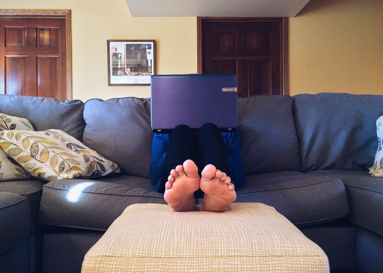 A man sits on a couch with a laptop in front of his face and his bare feet sticking up