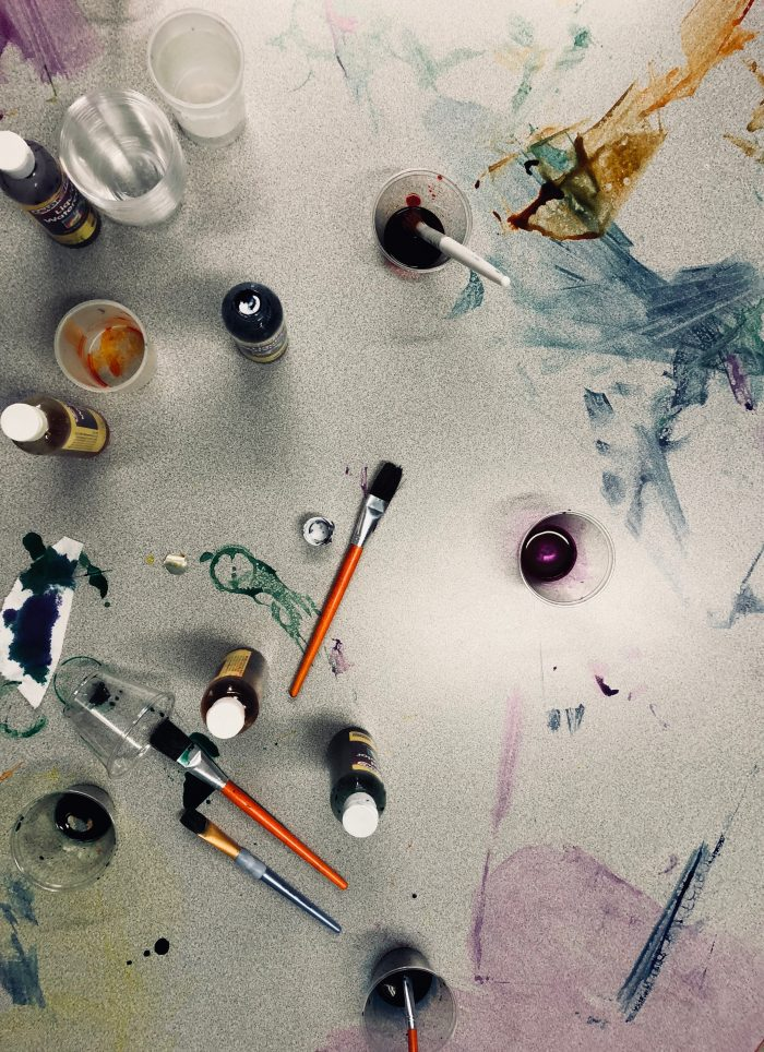 Paint brushes and cups full of paint on a messy surface.