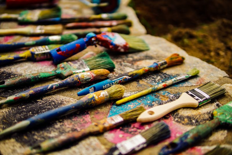 A bunch of colourful, used paint brushes on a bench top.