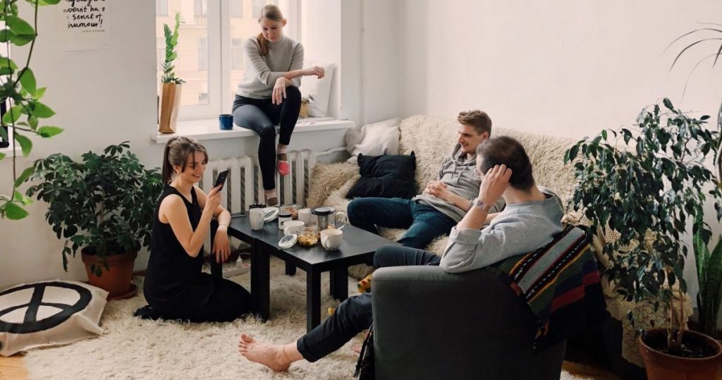 Four housemates relaxing in a living room