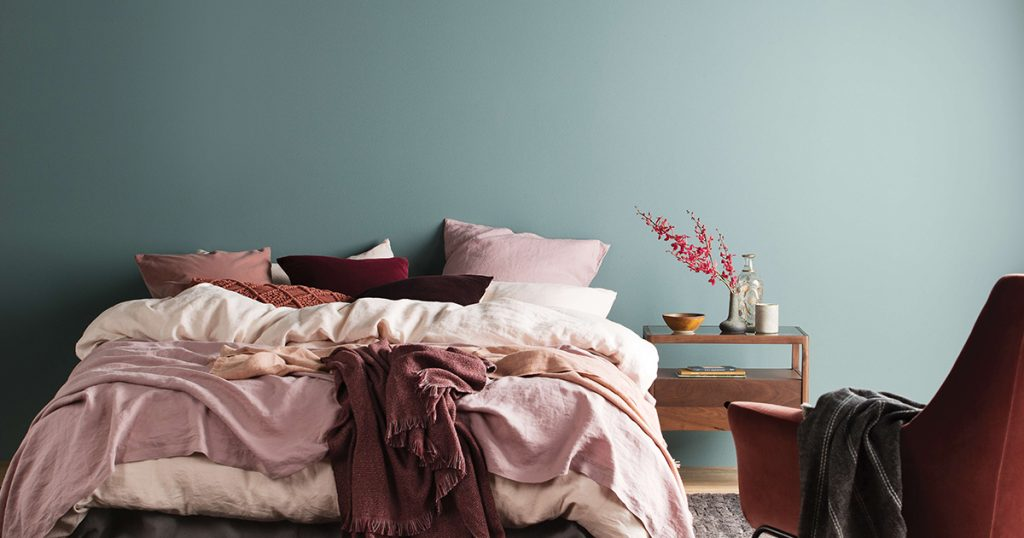 A bedroom with a blue-green feature wall and pink bedding.