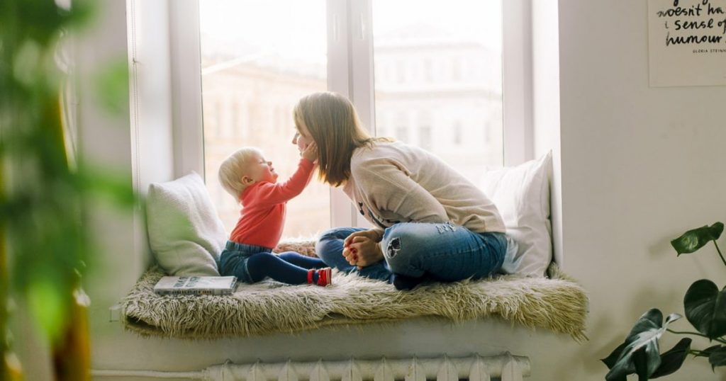 A mother and child sitting on a window sill