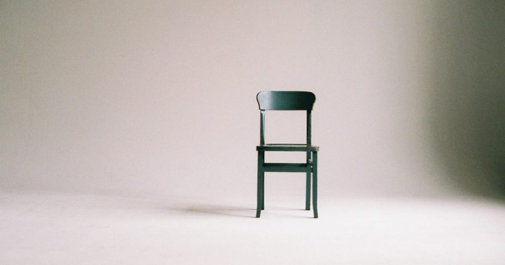 A singly grey chair against a grey background