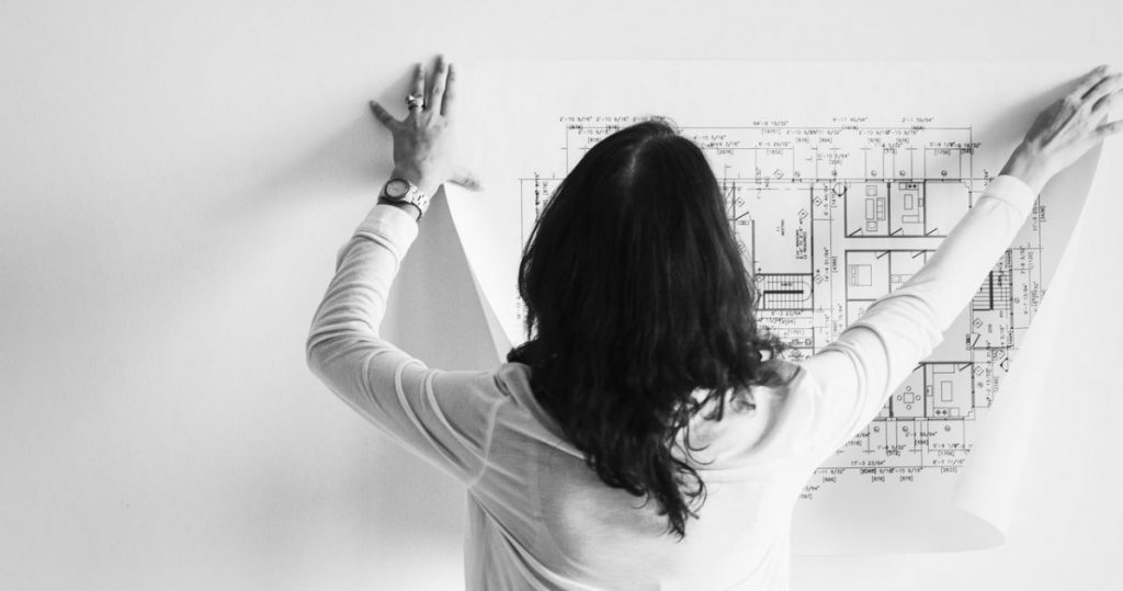 woman holding up architectural plans
