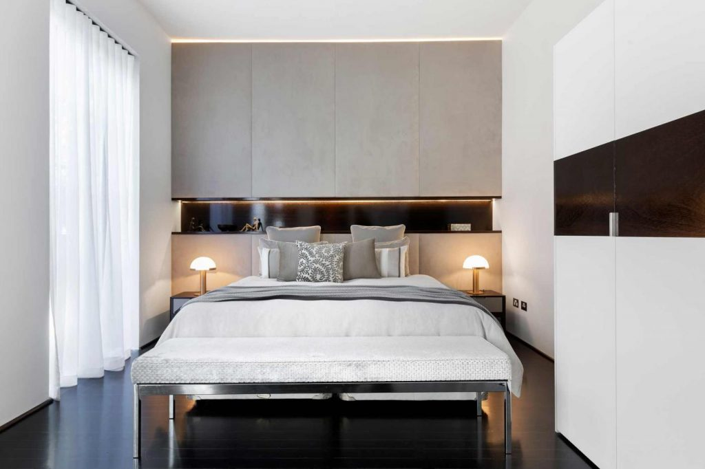 A designer bedroom with flowy window furnishing for a breezy finish.