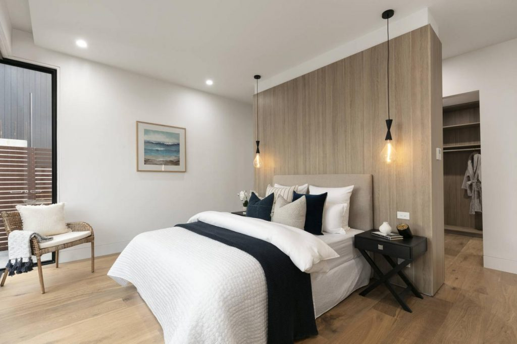 A modern bedroom with pendant lighting and downlights