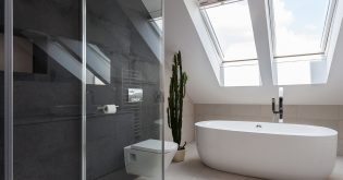 A modern bathroom with freestanding bath, shower, toilet and skylight
