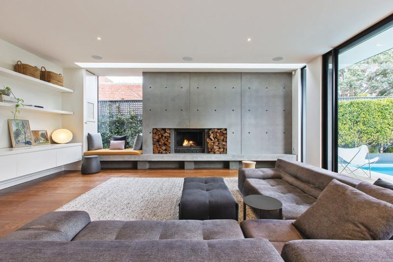 A living room with concrete wall and fireplace.