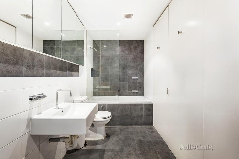 A modern bathroom with dark tiles and light walls.